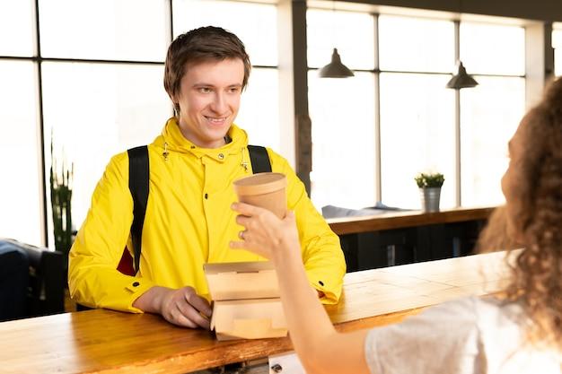 Szczęśliwy młody kurier w żółtej kurtce bierze dwa pojemniki z zamówionym jedzeniem i piciem dla klientów stojąc przed kelnerką