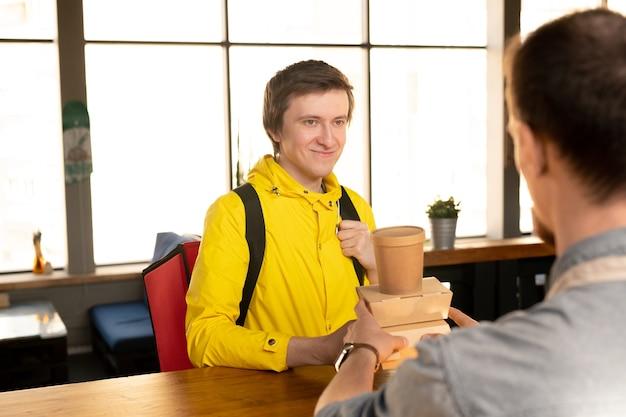 Szczęśliwy młody kurier z dużym plecakiem patrzy na kelnera, podając mu pojemniki z zamówionym jedzeniem i szklanką napoju w kawiarni