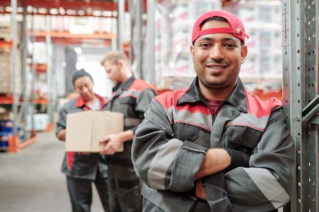 Szczęśliwy młody latynoski mężczyzna w odzieży roboczej i rękawiczkach krzyżujących ręce przez klatkę piersiową, stojący naprzeciw swoich kolegów pracujących w magazynie