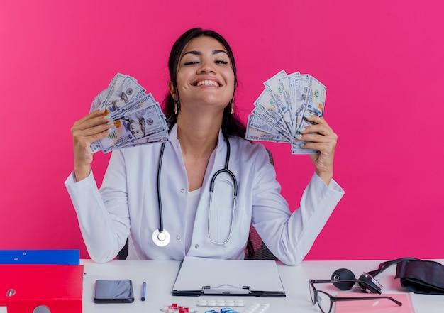 Szczęśliwy młody lekarz kobiet na sobie szlafrok medyczny i stetoskop siedzi przy biurku z narzędzi medycznych trzymając pieniądze na białym tle na różowej ścianie