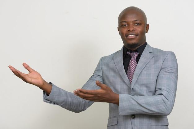 Szczęśliwy młody łysy biznesmen afrykański pokazuje coś