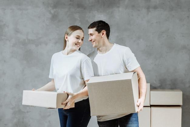 Szczęśliwy młody małżeństwo mężczyzna i kobieta z pudełkami