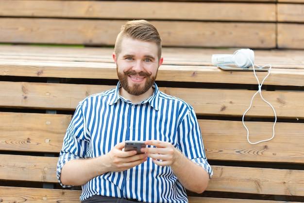 Szczęśliwy młody mężczyzna hipster student z wąsami i brodą, pisząc wiadomość sms do swoich przyjaciół