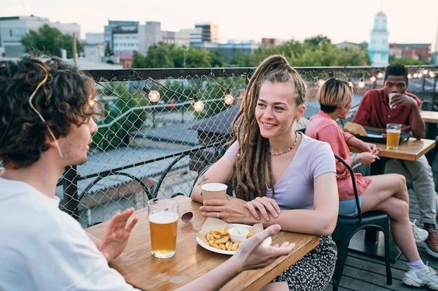 Szczęśliwy młody mężczyzna i kobieta o dacie w kawiarni na świeżym powietrzu