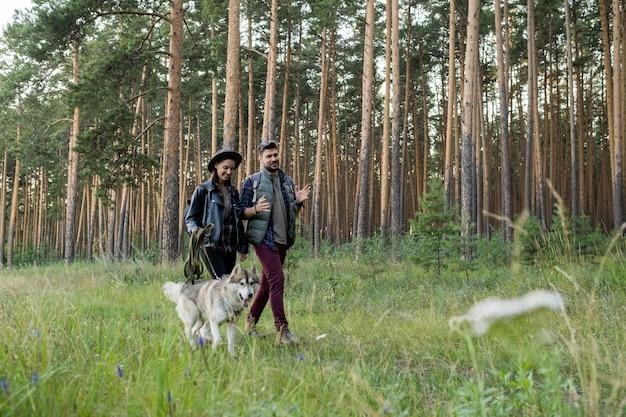 Szczęśliwy młody mężczyzna i kobieta rozmawiają na czacie podczas poruszania się po ścieżce