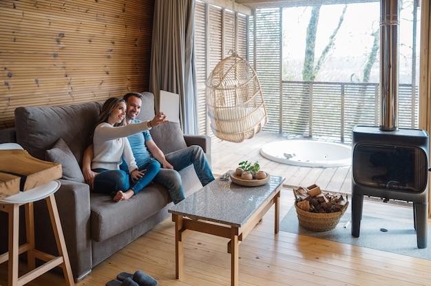 Szczęśliwy młody mężczyzna i kobieta w ubranie, siedząc na kanapie i biorąc selfie na tablecie, spędzając wolny czas razem w przytulnym salonie w stylu rustykalnym