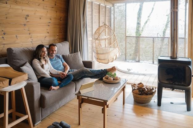 Szczęśliwy młody mężczyzna i kobieta w ubranie, siedząc na kanapie i oglądając film na tablecie, spędzając wolny czas razem w przytulnym salonie w stylu rustykalnym