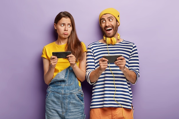 Szczęśliwy młody mężczyzna i smutne blogerki używają smartfonów do komunikacji online, grają w gry, są uzależnieni od nowoczesnych technologii
