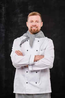 Szczęśliwy młody mężczyzna kucharz z rękami skrzyżowanymi w klatce piersiowej, patrząc na ciebie, stojąc na czarnym tle