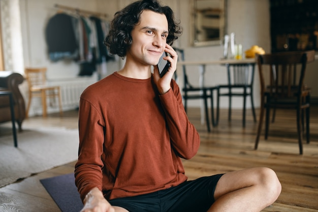 Szczęśliwy młody mężczyzna w ubranie spędzający cały dzień samotnie w domu, dystansując się, uśmiechając się