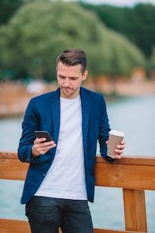 Szczęśliwy młody miastowy mężczyzna pracuje kawę w europejskim mieście outdoors i pije