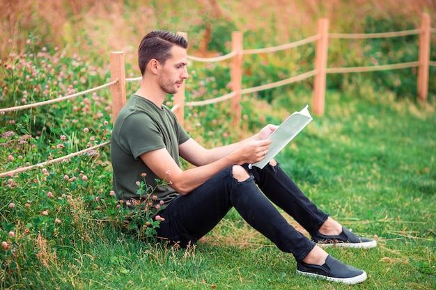 Szczęśliwy młody miastowy mężczyzna z książką outdoors