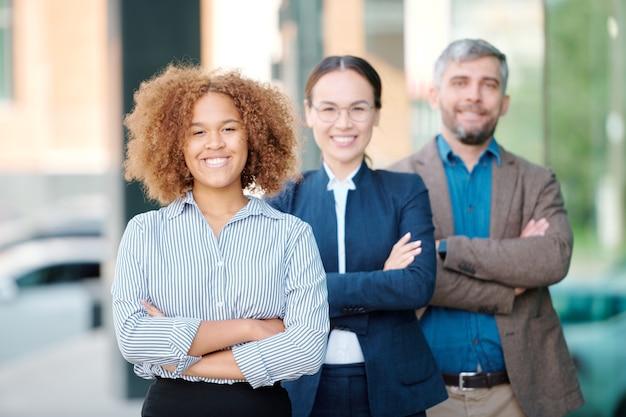 Szczęśliwy młody międzykulturowy lider zespołu współczesnego biznesu, krzyżując ramiona na piersi, stojąc przed kolegami