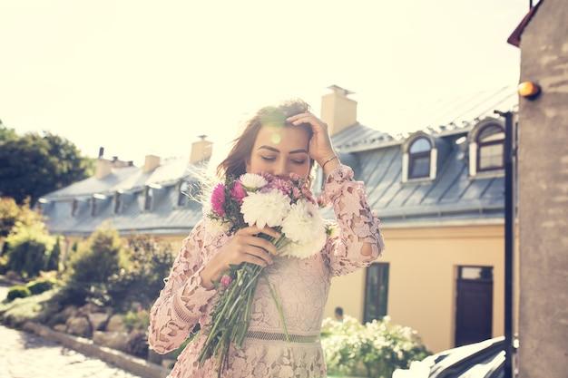 Szczęśliwy młody model w różowej sukience z kwiatami w ręce na tle miasta. efekt tonowania w stylu vintage