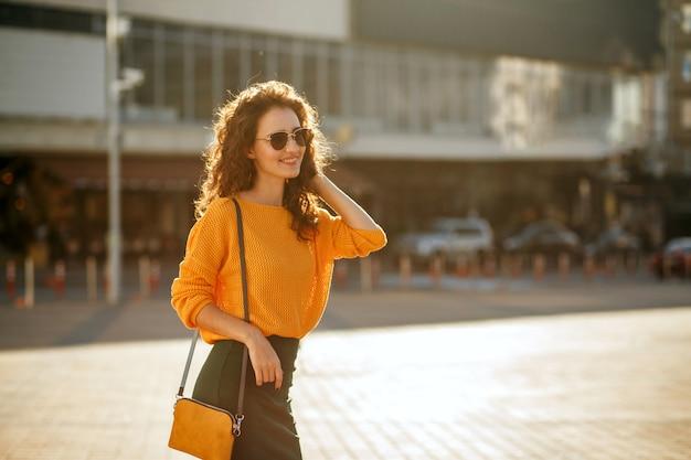 Szczęśliwy młody model z kręconymi włosami w okularach przeciwsłonecznych na sobie modny strój i spaceru na słonecznej ulicy. miejsce na tekst