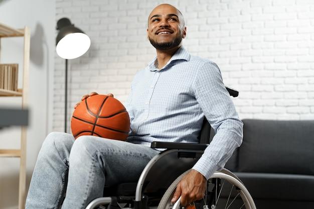 Szczęśliwy młody niepełnosprawny mężczyzna na wózku inwalidzkim, trzymający piłkę do koszykówki i uśmiechnięty