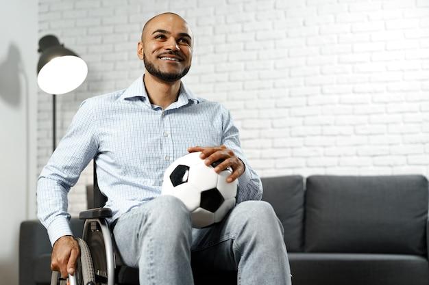 Szczęśliwy młody niepełnosprawny mężczyzna na wózku inwalidzkim, trzymający piłkę nożną i uśmiechnięty