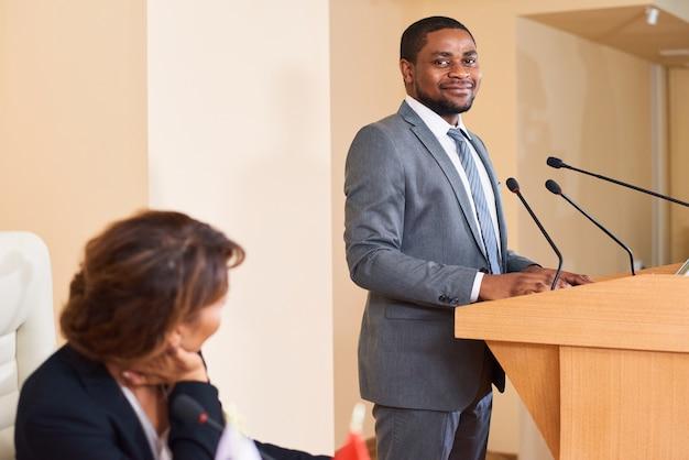 Szczęśliwy młody, odnoszący sukcesy mówca w eleganckim garniturze, patrząc na ciebie stojąc obok trybuny przed publicznością na konferencji