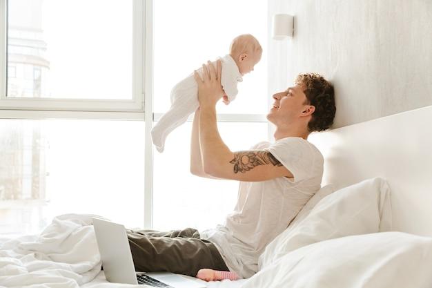 Szczęśliwy młody ojciec bawi się ze swoim małym synkiem, leżąc w łóżku w domu, obejmując