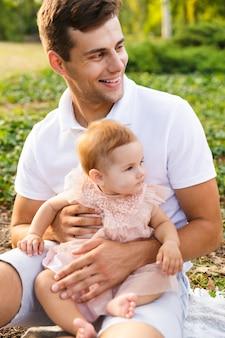 Szczęśliwy młody ojciec bawi się ze swoją małą córeczką