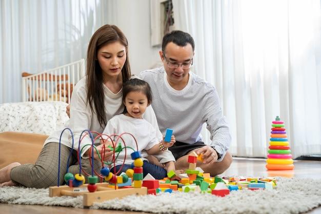 Szczęśliwy młody ojciec i matka oraz mała córka bawi się drewnianymi klockami zabawek, siedząc na podłodze w salonie, rodzinie, rodzicielstwie i koncepcji ludzi z zabawkami rozwojowymi