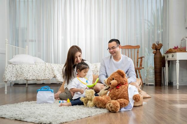 Szczęśliwy młody ojciec i matka oraz mała córka bawi się zabawką, siedząc na podłodze w koncepcji salonu, rodziny, rodzicielstwa i ludzi