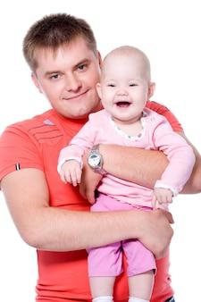 Szczęśliwy młody ojciec trzyma swoje dziecko z atrakcyjnym uśmiechem