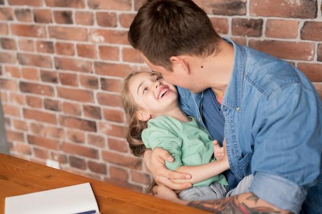 Szczęśliwy młody ojciec w dżinsowe koszule siedzi przy stole i przytulanie, śmiejąc się, piękna córka, spędzając wolny czas w domu