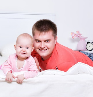 Szczęśliwy młody ojciec z uśmiechniętym dzieckiem leżącym na łóżku w sypialni