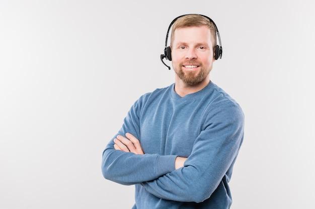 Szczęśliwy młody operator w słuchawkach krzyżujący ramiona przy klatce piersiowej, patrząc na ciebie w izolacji