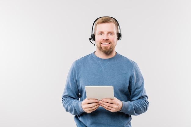 Szczęśliwy młody operator w słuchawkach za pomocą cyfrowego tabletu, patrząc na ciebie i konsultując się z klientami w izolacji