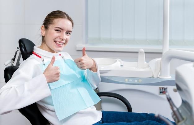 Szczęśliwy młody pacjent u dentysty