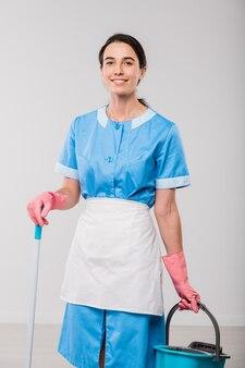 Szczęśliwy młody personel sprzątający pokój hotelowy w rękawiczkach mundurowych i gumowych, trzymając wiadro i mop, stojąc przed kamerą w izolacji