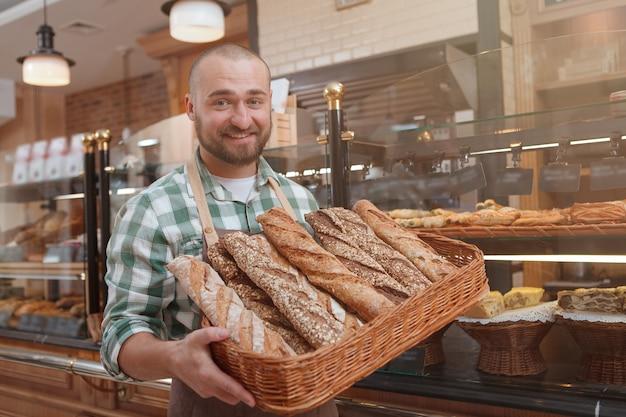 Szczęśliwy młody piekarz mężczyzna uśmiecha się do kamery, niosąc w koszu świeżo upieczony chleb
