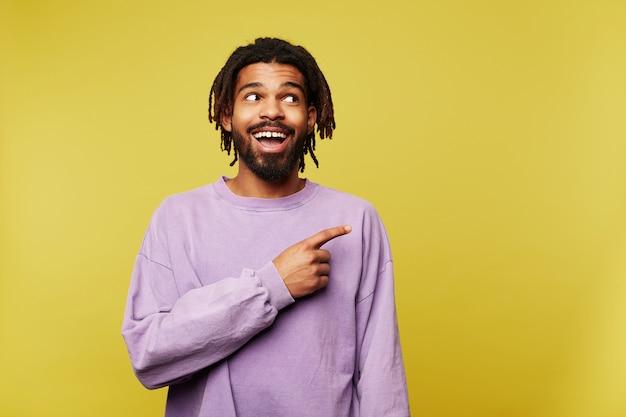 Szczęśliwy młody piękny ciemnoskóry brunet brodaty mężczyzna wskazujący aisde z palcem wskazującym i uśmiechnięty szeroko, ubrany w zwykłe ubrania, stojąc na żółtym tle