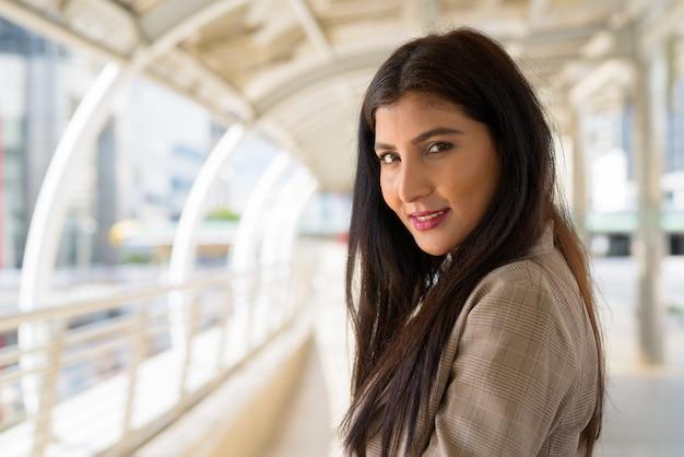 Szczęśliwy młody piękny indyjski bizneswoman uśmiecha się do kładki w mieście