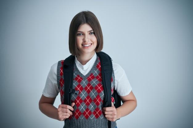 Szczęśliwy młody pozytywny student pozowanie na jasnym tle