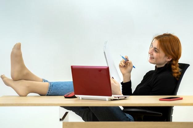 Szczęśliwy młody pracownik biurowy kobieta siedzi zrelaksowany z nogami na stole za biurkiem z laptopa