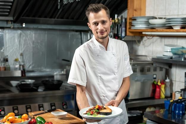 Szczęśliwy młody profesjonalny szef kuchni w białym mundurze trzymającym talerz z kawałkiem smażonego łososia i posiekanymi warzywami na parze w środowisku kuchennym