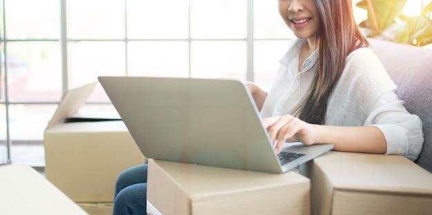 Szczęśliwy młody przedsiębiorca kobieta azji, uśmiech na sukces sprzedaży po sprawdzeniu zamówienia w sklepie internetowym w laptopie w biurze domowym