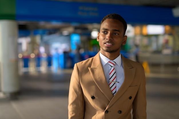 Szczęśliwy młody przystojny afrykański biznesmen odchodząc z dworca kolejowego