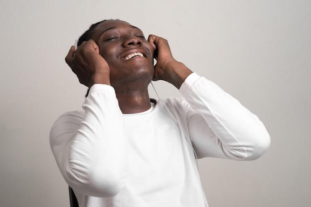 Szczęśliwy młody przystojny afrykański mężczyzna z dredami, słuchanie muzyki
