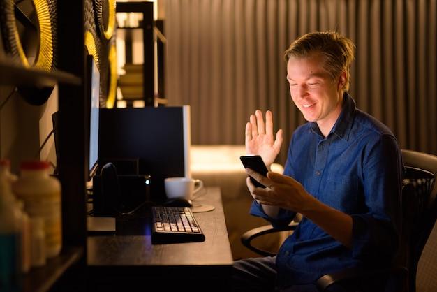 Szczęśliwy młody przystojny biznesmen rozmowy wideo podczas pracy w domu w nocy