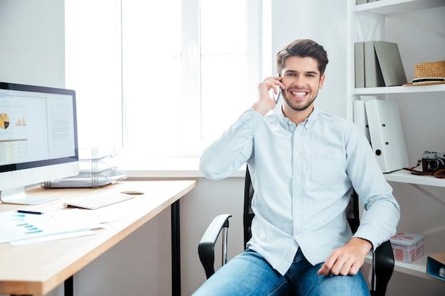 Szczęśliwy młody przystojny biznesmen siedzi w swoim miejscu pracy w biurze i rozmawia przez telefon komórkowy