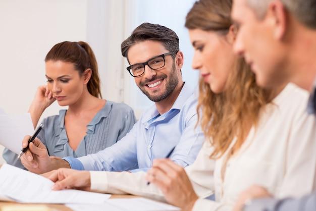 Szczęśliwy młody przystojny biznesmen w spotkaniu na sobie okulary. sukcesy biznesmen pisze ważne informacje na konferencji. portret biznesmena uśmiecha się podczas spotkania biznesowego.
