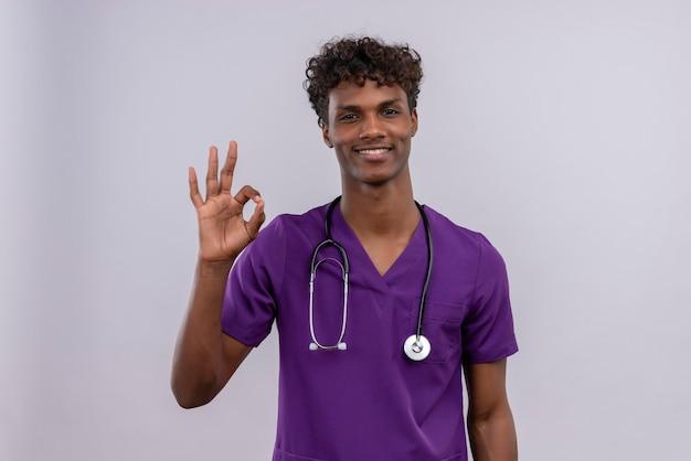 Szczęśliwy młody przystojny ciemnoskóry lekarz z kręconymi włosami ubrany w fioletowy mundur ze stetoskopem pokazującym znak ok rękami