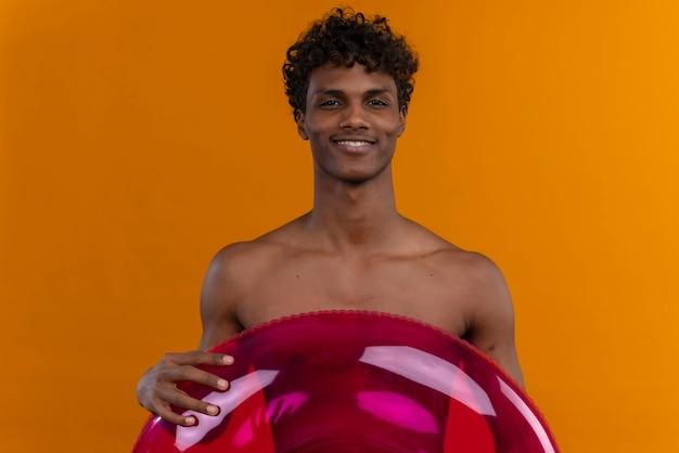 Szczęśliwy młody przystojny ciemnoskóry mężczyzna z kręconymi włosami trzyma nadmuchiwany pierścień basenowy