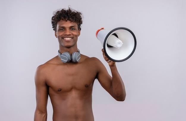 Szczęśliwy młody przystojny ciemnoskóry mężczyzna z kręconymi włosami w słuchawkach trzymając megafon podczas