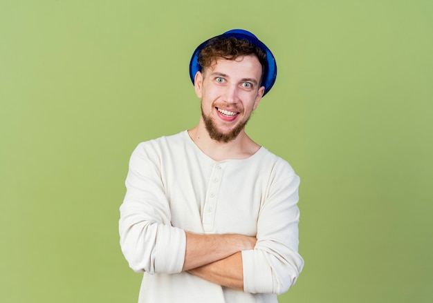 Szczęśliwy młody przystojny facet słowiańskich partii na sobie kapelusz partii stojącej z zamkniętą posturą patrząc na kamery na białym tle na oliwkowym tle z miejsca kopiowania
