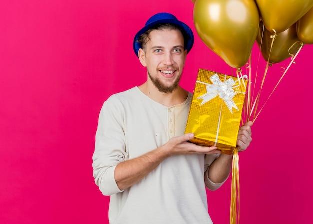 Szczęśliwy młody przystojny facet słowiańskich partii noszenie kapelusza strony, trzymając balony i pokazując pudełko patrząc z przodu na białym tle na różowej ścianie z miejsca na kopię